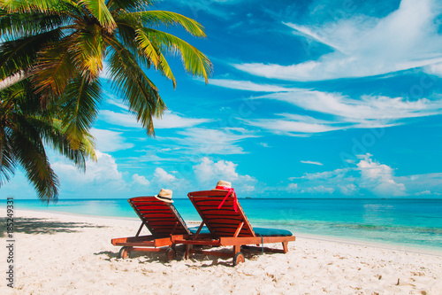 Fototapeta Two beach chairs on tropical vacation