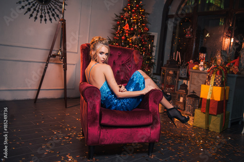 beautiful sexy woman sit in the red chair glamour blond girl in sexy dress and high heel shoes fashion