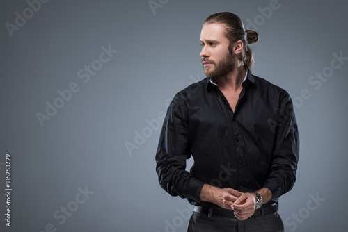 Fotografie, Obraz  Handsome bearded man in black shirt looking away, isolated on gray