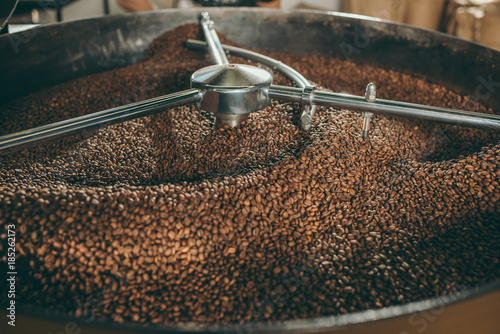 Fotografija close up view of coffee beans roasting in machine
