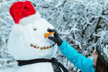 Woman Making Snowman In Winter...