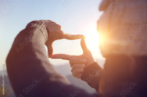 Fotografiet  Close up of woman hands making frame gesture with sunrise on moutain, Female capturing the sunrise, Future planning, sunlight outdoor