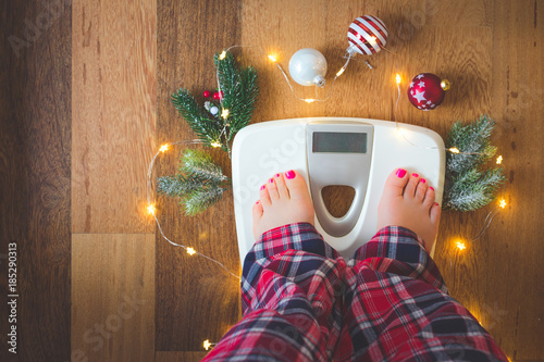 Fototapeta Top view of female feet in winter pajamas on digital scales or weight scale on wooden background surrounded with Christmas lights and decoration. Weight gain during holidays concept, vintage toned obraz