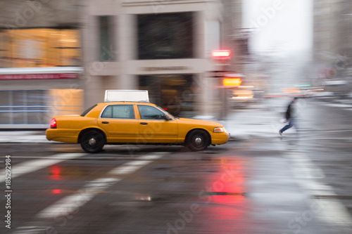 Cuadros en Lienzo Panning motion image of a New York City yellow taxi cab in the snow as it passes