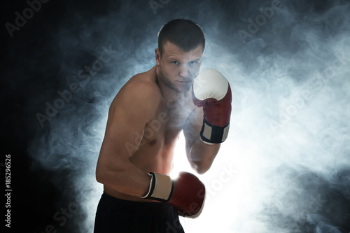 Fotografía  Young male boxer with smoke on background