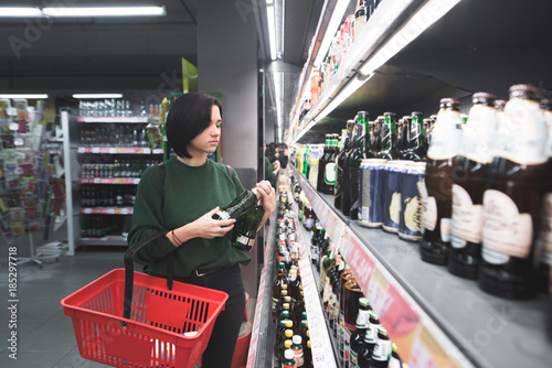 Poster de jardin Bar A girl with a red basket chooses alcohol in a supermarket. Shopping for beer at the store. The girl is shopping at the supermarket.