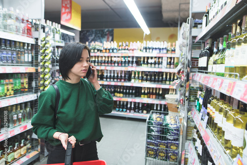 Poster de jardin Bar A young girl calls on the phone and chooses products in the supermarket. A beautiful girl is consulting with shopping on the phone. Shopping in a supermarket.