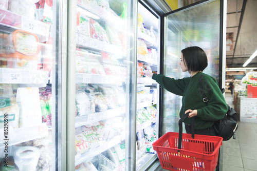 A girl with a basket takes frozen foods from the supermarket's refrigerator Canvas Print