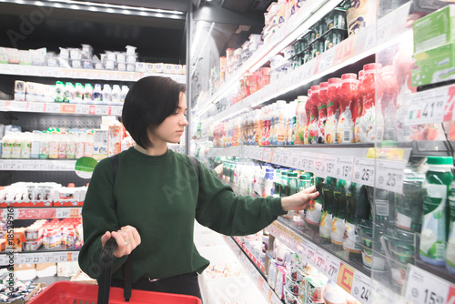 Poster de jardin Bar The girl buys yogurt in the milk department of the supermarket. The choice of goods in the store. Shopping in a supermarket.