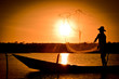 Homem jogando redes em pôr do sol