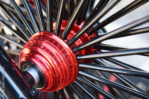 Fotografie, Obraz  Chopper motorcycle wheel, red hub and black shiny spokes.