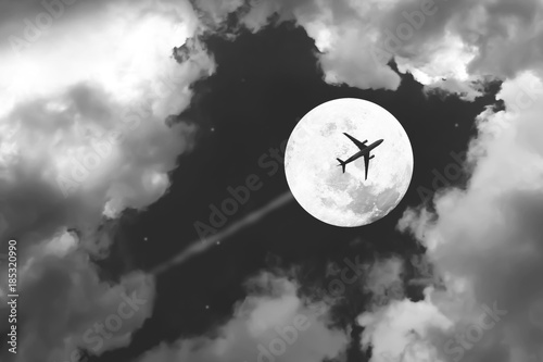 Fotografiet  Beautiful dramatic atmosphere of airplane in black and white night sky with jet and full moon night