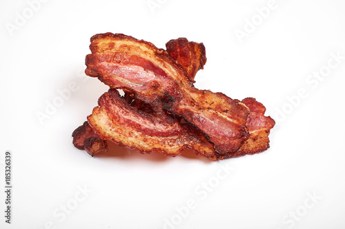 Three cooked, crispy fried bacon isolated on a white background. Canvas Print