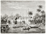 Ancient river in the jungle flowing near to a native Dayak people village, Borneo. Boats sailing and palms on background. Created by Francais after Schwaner published on Le Tour du Monde Paris 1862 - 185332753