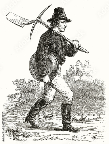 Ancient gold prospector walking and holding pan shovel and pick, outdoor in California Tablou Canvas