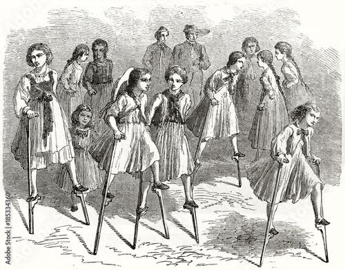 Valokuvatapetti Old illustration of girls playing on stilts
