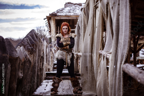 Photo  Viking woman with hammer in a traditional warrior clothes.