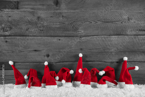 Cuadros en Lienzo Humorously red, grey and white wooden christmas background with santa hats
