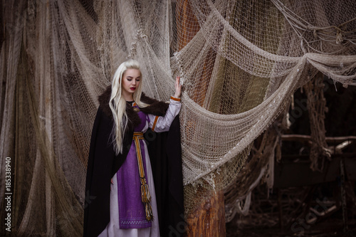 Outdoors portrait of beautiful furious scandinavian warrior ginger woman in a traditional clothes with fur collar, with sword in her hand and wooden Viking Village view on the background Wallpaper Mural