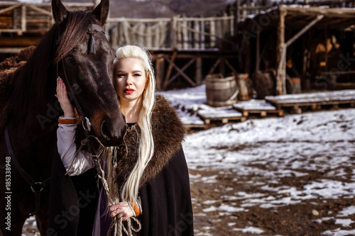 Photo  Outdoors portrait of beautiful furious scandinavian warrior ginger woman in a traditional clothes with fur collar, with sword in her hand and wooden Viking Village view on the background