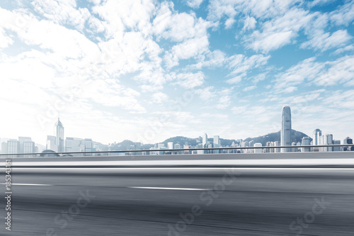 blurry empty asphalt road with modern cityscape Poster