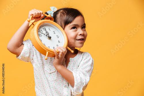 Fototapeta Cheerful little girl holding clock alarm. obraz