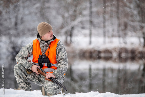 Male hunter in camouflage, armed with a rifle, sittiing in a snowy winter forest