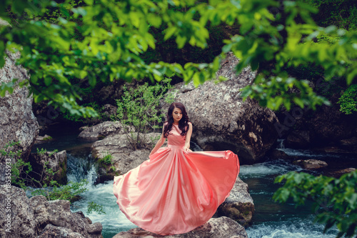 Fototapety, obrazy: River witch, sitting on a rock in river. Pink long dress, a fabulous image.Fashionable toning. Creative color.