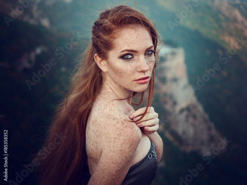 Foto  Summer outdoors portrait of beautiful furious scandinavian warrior ginger woman in grey dress with metal chain mail