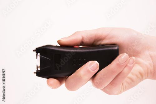 Fotografia, Obraz The girl's hand holds an Electroshocker