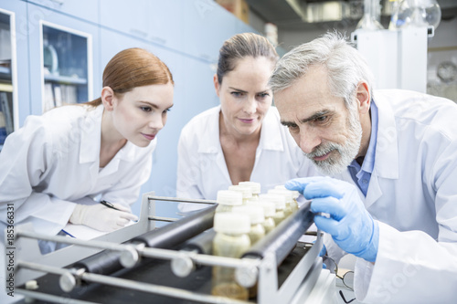 Three scientists in lab examining samples