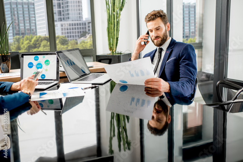 Handsome analytic manager working with paper charts and laptop at the luxury office interior
