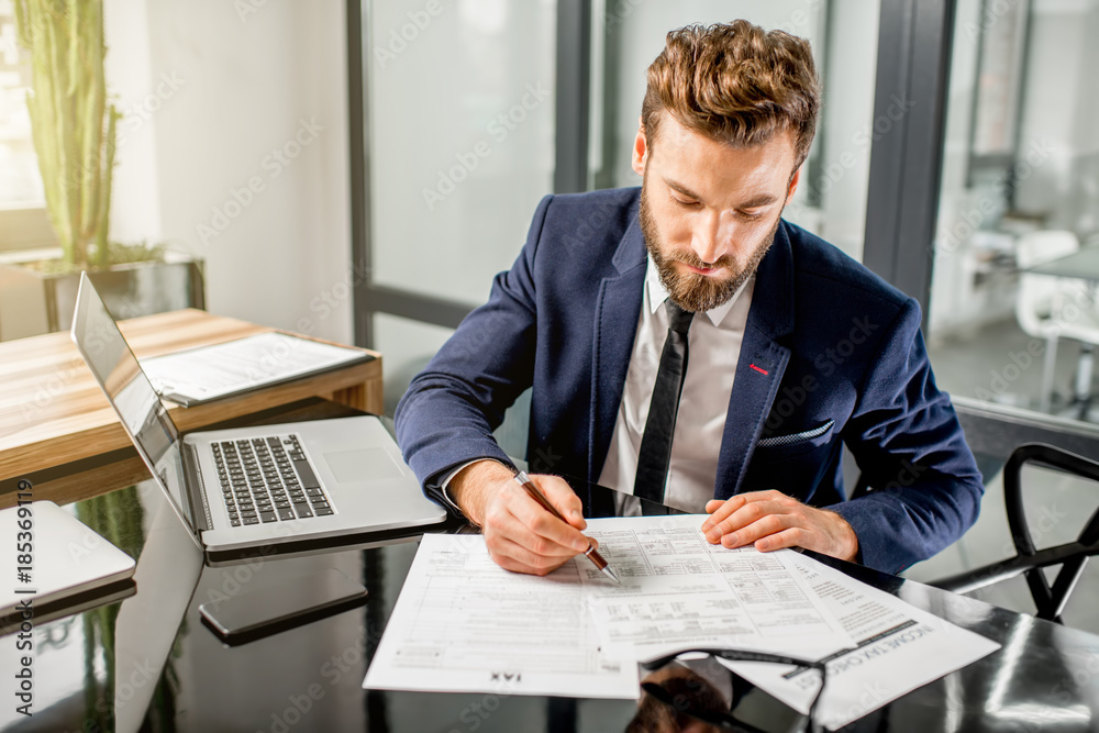 Fototapeta Handsome tax manager dressed in the suit working with documents and laptop at the modern office interior