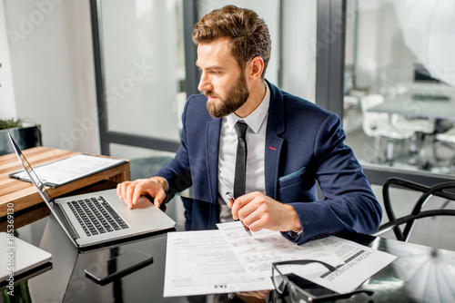 Photo  Handsome tax manager dressed in the suit working with documents and laptop at th
