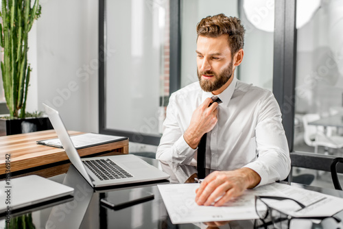 Fototapety, obrazy: Portrait of a tired tax manager taking off a tie while working with tax documents and laptop at the office