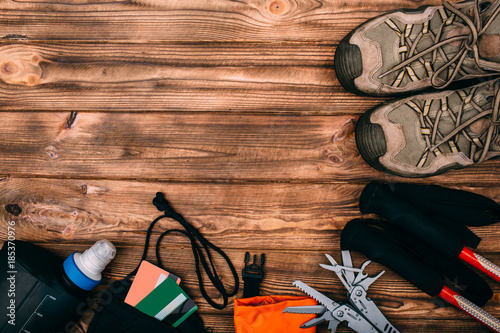 Top view of equipment for hiking and travel on wooden table withempty space in the middle. Items include trekking pole, shoes, multi tool, hat, towel, hermetic bag, payment card, water bottle