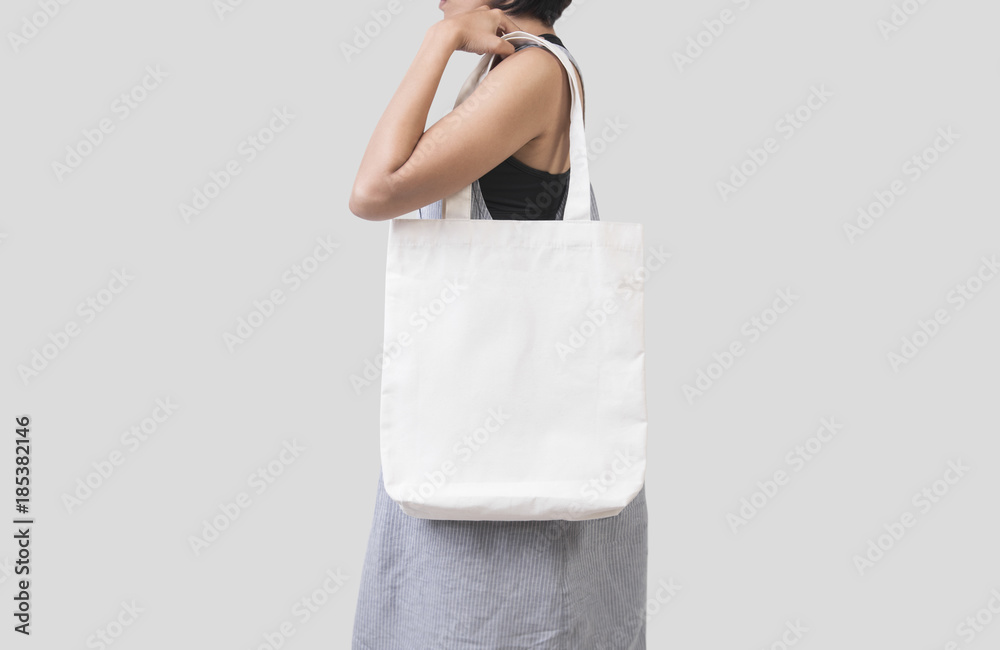 Fototapety, obrazy: Girl is holding bag canvas fabric for mockup blank template isolated on gray background.