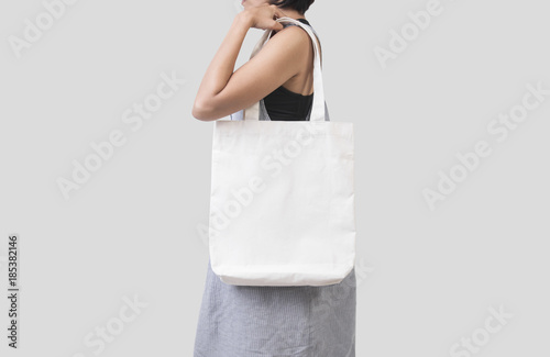 Photo Girl is holding bag canvas fabric for mockup blank template isolated on gray background