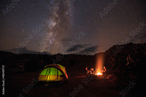 Poster Camping Family of four sitting around a campfire under stars and the milky way.