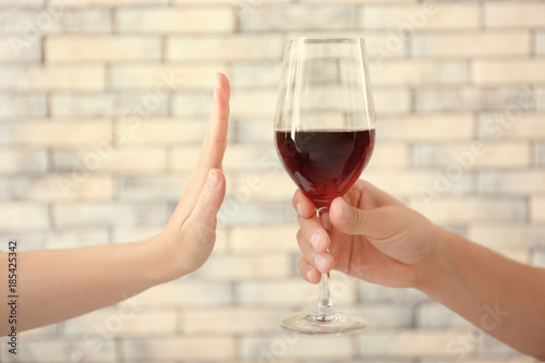 Fotobehang Alcohol Hand of woman refusing glass of alcohol against brick wall