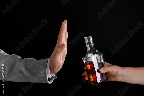 Spoed Foto op Canvas Bar Hand of man rejecting bottle of alcohol against dark background