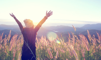 Happy Woman Enjoying Nature on grass meadow on top of mountain cliff with sunset outdoor. Freedom concept.