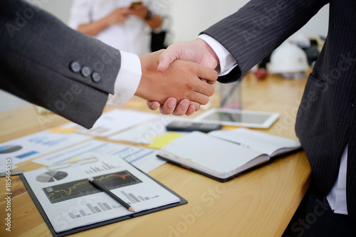 Photo acquisition business people shaking hands, finishing up a meeting