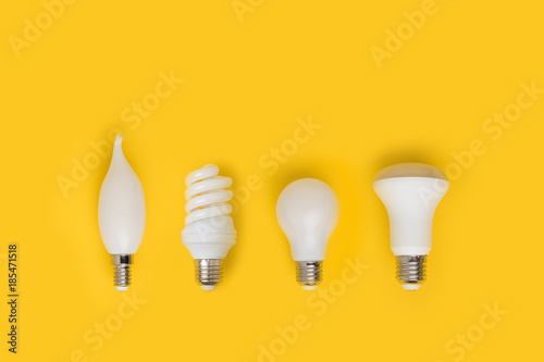 Photo  top view of set of different white lamps isolated on yellow