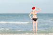 Girl in Santa hat and bathing suit looks into the distance. Sea shore.