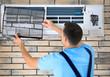 Male technician repairing conditioner indoors