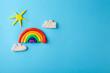 Plasticine rainbow, sun and clouds on color background