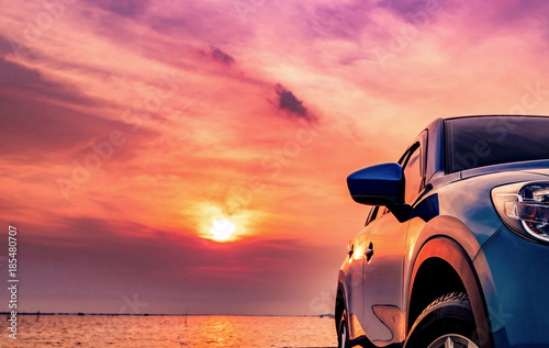 Poster Corail Blue compact SUV car with sport and modern design parked on concrete road by the sea at sunset. Environmentally friendly technology. Business success concept.