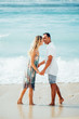 Happy Couple Holding Hands and Kissing on Beach