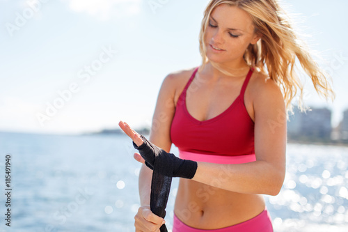 Photo  Young blonde woman wrapping bandage on hands at seashore